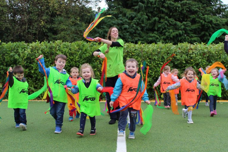 kids carrying colourful ribbons running on astro