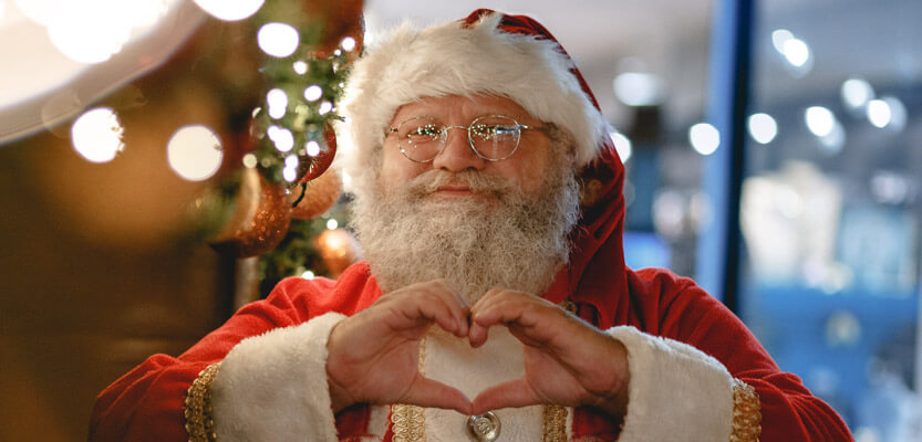 santa claus making a love heart shape with his hands